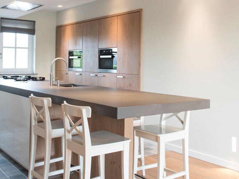 Een woonkeuken met betonnen blad en pittcooking